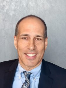 Photo of man, Chris Gallo in a suit with a gray background
